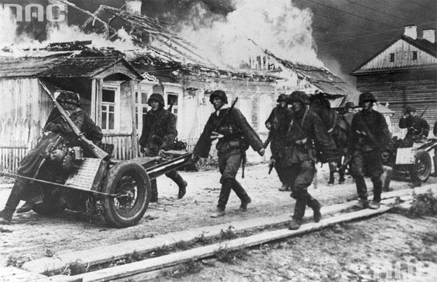 Oddział Waffen-SS na tle płonących zabudowań /Z archiwum Narodowego Archiwum Cyfrowego/