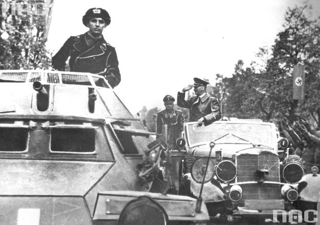 Adolf Hitler w Warszawie pozdrawia z samochodu mercedes salutujących żołnierzy. Na pierwszym planie wóz pancerny SdKfz 222 /Z archiwum Narodowego Archiwum Cyfrowego/
