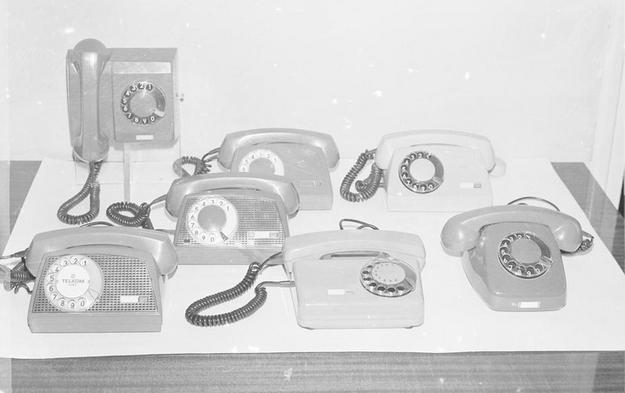 Aparaty telefoniczne. W pierwszym szeregu od lewej: Storczyk, Tulipan, Jaskier. W drugim szeregu Storczyk. W trzecim szeregu od prawej dwa aparaty Aster. Z tyłu jedyny wiszący aparat Irys (1976) /Z archiwum Narodowego Archiwum Cyfrowego/