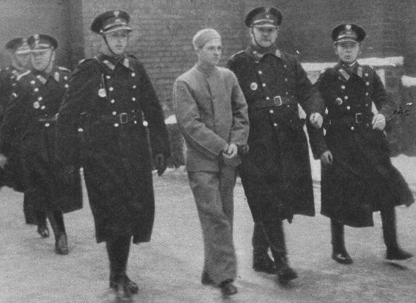"""Nikifor Maruszeczko eskortowany przez policjantów fot. """"Światowid"""" /Wikimedia/"""